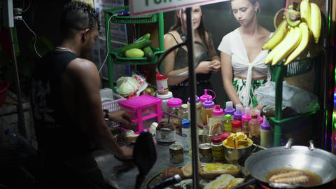 Burmese pancake maker selling food in food cart with western girls watching Live Action
