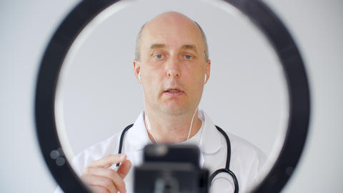 Professional male doctor in earphones recording blog and talking at camera GIF