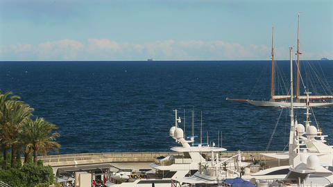 View of sailboat is on horizon through masts of yachts, luxury life Live Action