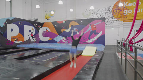 Guy doing acrobatic trick on trampolines Live Action