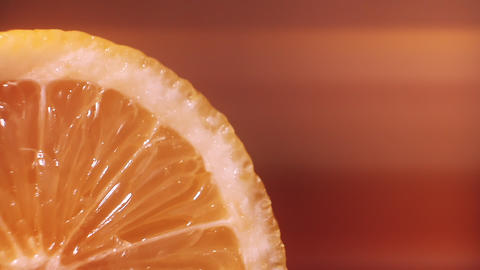 A slice of lemon is watered with water, macro closeup. Healthy food Live Action