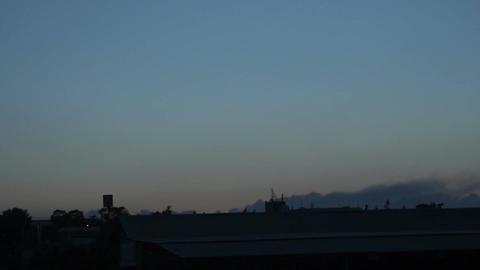 Time lapse of wildfire raging on horizon, dusk in village, establishing shot Footage