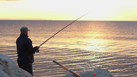 Man fishing at seaside, enjoying tranquil hobby on vacation, beautiful sunrise Footage