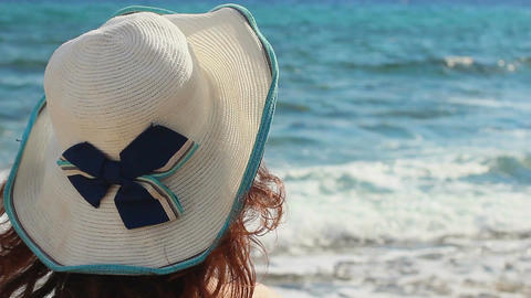 Closeup of brunette female in hat looking at sea waves, enjoying summer vacation Footage