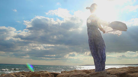 Silhouette of free woman in sunlight, beautiful seascape, sun hiding in clouds Footage