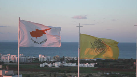 Flags of Cyprus and Greek Orthodox Church waving in wind, seascape on background Footage