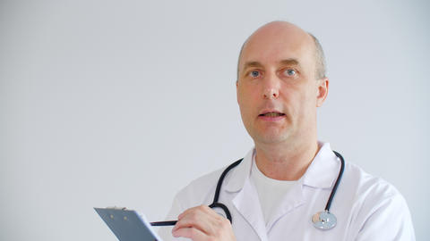 Professional male doctor holding clipboard with pen and talking about diagnosis Live Action