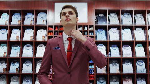 Young man try on classical suit in the suit shop Live Action