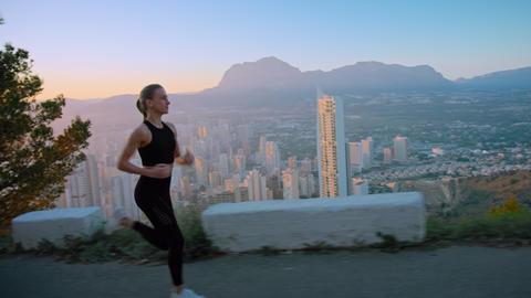 Fit healthy sport woman run over city at sunrise ライブ動画