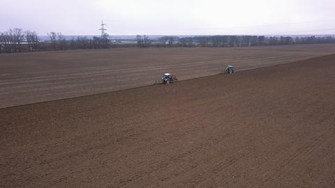 Agricultural work in the field, two blue tractors plow the land Acción en vivo