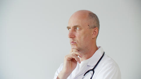 Pensive confident male doctor standing with hand on chin and thinking about GIF