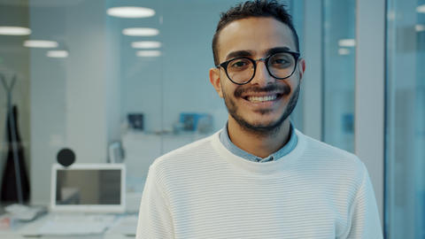 Portrait of handsome Arab man office worker standing in workplace smiling Live Action