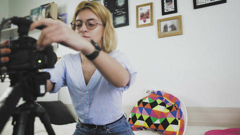 Female blogger turns on the camera and starts talking. Making video blog at home Live Action