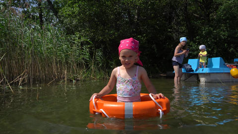 Cute girl wade in water with swimsuit and lifebuoy. Mother with little boy ライブ動画
