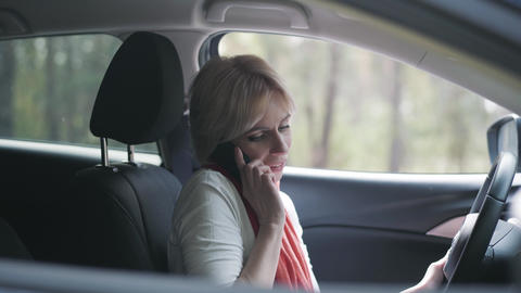 Portrait of confident female driver talking on the phone and applying lipstick Live Action