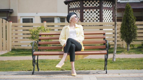 Camera approaches to cheerful relaxed woman sitting on bench on residential Live Action
