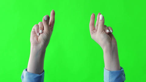 Woman hand snaps her fingers over green background. Snapping fingers of Live Action