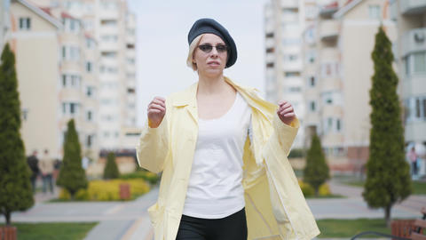 Beautiful confident blond woman walking and taking off sunglasses. Portrait of Live Action
