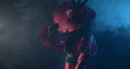 Profile shot of a woman in red dress with a hat, Santa Muerte skull on her face Live Action