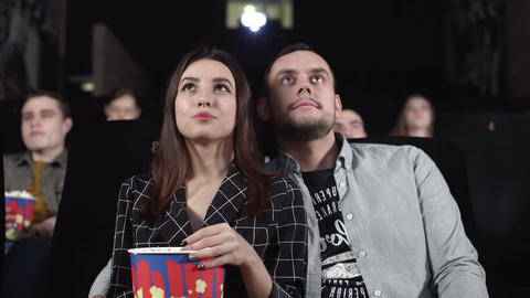 Love couple watching movie and eating popcorn in cinema theatre. Movie GIF