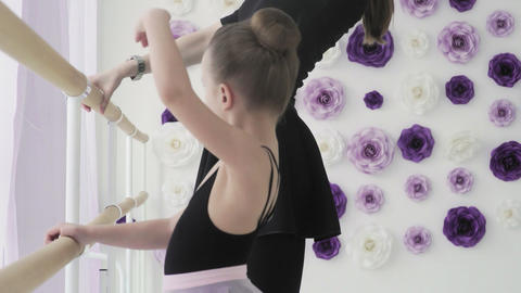 Cute ballerina repeats the movements with the teacher GIF