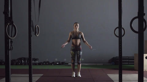 Young adult sporty woman performing skipping rope workout in cross fit gym Live Action
