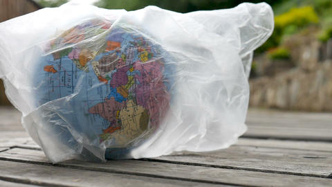 Side view of the Earth in polyethylene disposable package on wooden background ライブ動画