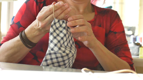 Mature woman is making home made breathing mask, corona virus protection Live Action