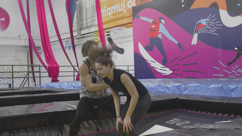 The coach teaches the novice acrobat how to land on a trampoline Live Action