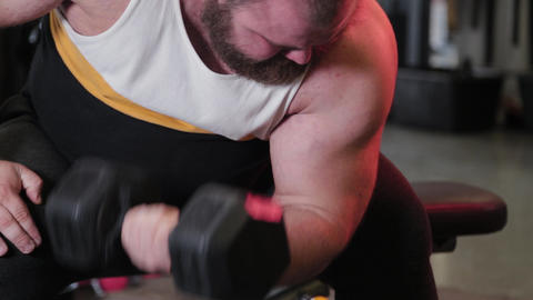 Big and powerful athlete trains dumbbell biceps in a sports club ライブ動画