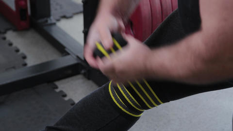 Big and powerful weightlifter wraps elastic hard bandages on his knees ライブ動画