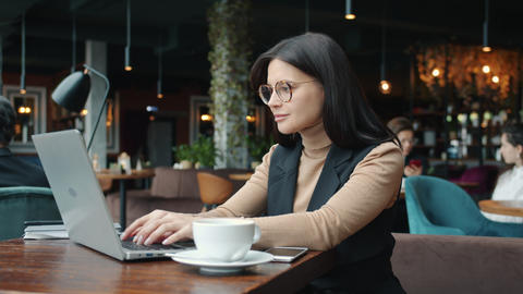 Young attractive businesslady using laptop computer typing in restaurant alone Live Action