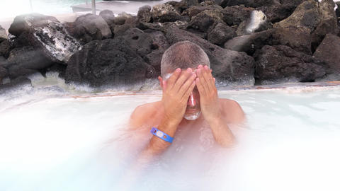 Man spreading cream on his face in a hot thermal bath. Slow motion. Sun light ライブ動画