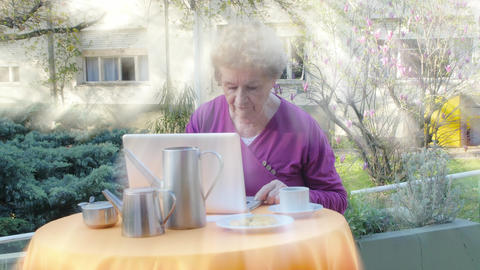 Active elderly woman using modern laptop making breakfast outdoor. Light rays Live Action