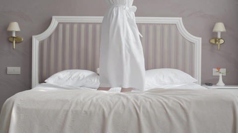 Cheerful unrecognizable Caucasian woman jumping on bed in hotel room. Slim girl Live Action