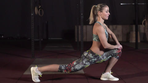 Athletic active woman doing stretching exercises in a Loft Style Industrial Gym Live Action