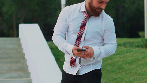 Attractive businessman looking at a mobile phone, feeling happy and leaving Live Action