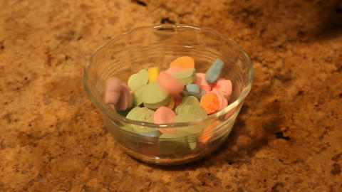Valentine candy hearts slow drop into bowl P HD Footage
