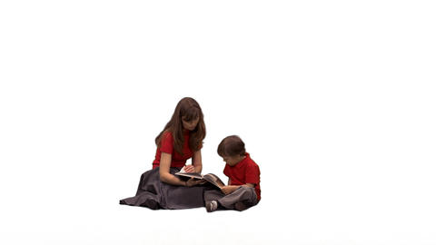 A lovely child listening to his mother reading a book, alpha channel Footage