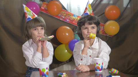 Young beautiful twin girls blowing party horns Footage
