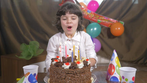 Young beautiful girl blowing candles on a birthday cake Footage