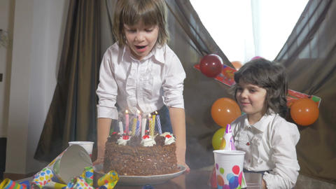 4k - Young beautiful girl blowing candles on a birthday cake with her twin siste Footage