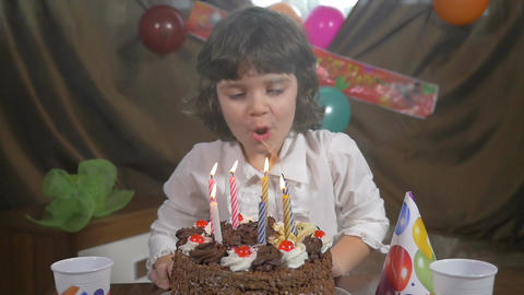 Young beautiful girl blowing candles on a birthday cake, slow motion Footage