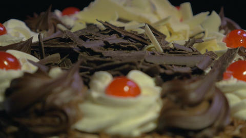 4k - Detail of a delicious chocolate cake spinning on a black background Footage