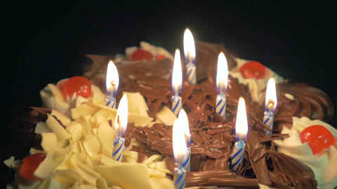 4k - Blowing out birthday candles on a spinning delicious chocolate cake Footage