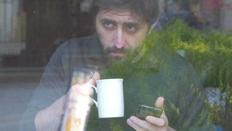 Man using his smartphone and drinking in a coffee shop Footage