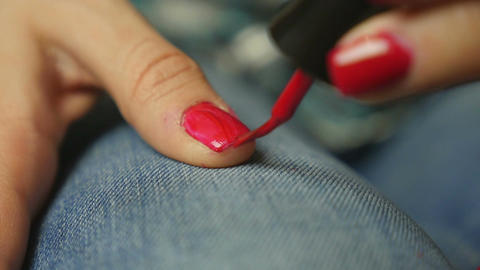 Young woman coloring her nails with red nail polish ビデオ