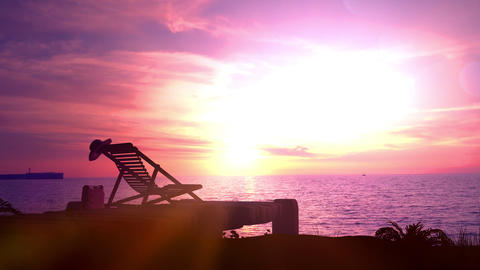 Empty beach and deckchair on a sunset background Live Action
