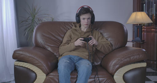 Portrait of addicted teenager gaming online. Pale Caucasian boy in headphones Live Action