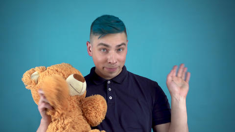 A young man with blue hair is holding a teddy bear. Alternative man waves his Live Action